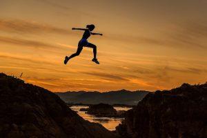 Woman jumping between hills