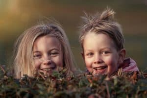 two happy kids looking over a bush
